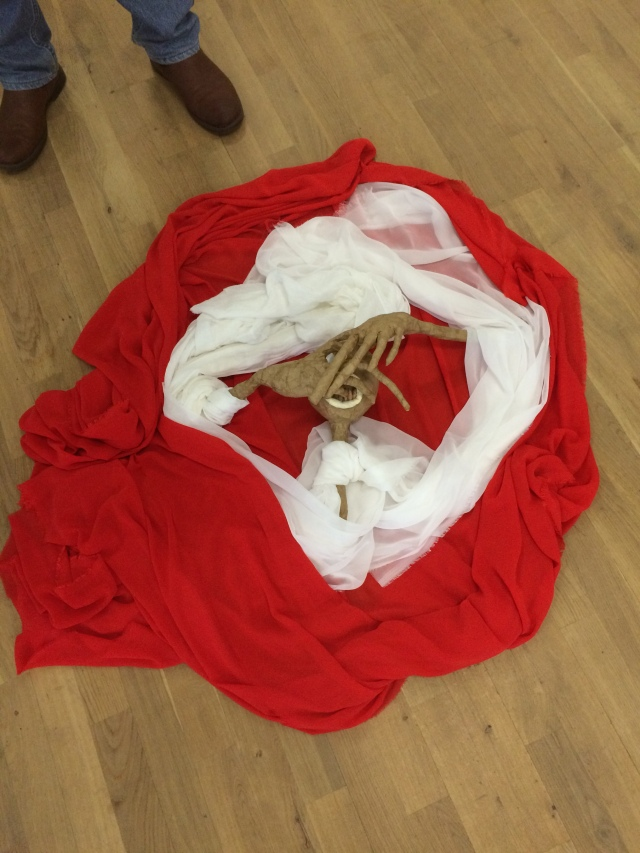 A puppet tablau with red and white cloth surrounding a puppet covering its face with its hands, from a puppetry with trauma victims workshop