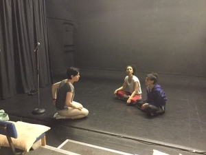 The director and two dancers sit on the stage in a black studio theatre, while the director gives notes