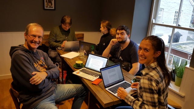 Writers from the Cornwall Wrimos sitting around a table in a coffee shop with laptops and coffee